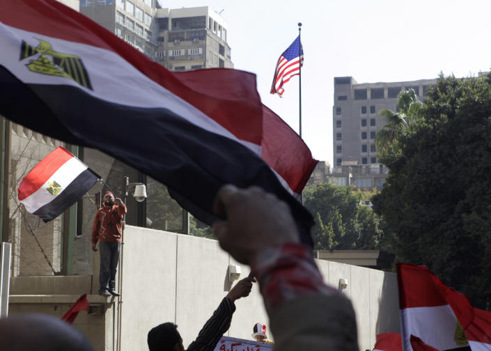 Egyptian protesters wave their national flags in front of the American embassy in Cairo, Egypt, Friday March 9, 2012 as they protest against what they say is American intervention in Egypt. Several hundred protesters gathered Friday outside the U.S. Embassy in Cairo, raising their shoes at a picture of President Barack Obama and calling on Egypt to expel Washington's ambassador amid a heated national debate about the trial of Americans working with pro-democracy groups who have been charged with using foreign funding to foment unrest. (AP Photo/Amr Nabil)