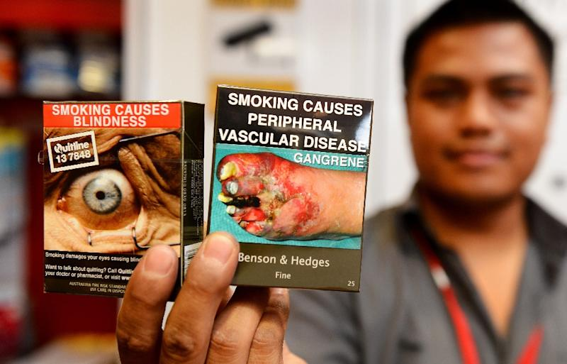 A shop owner in Sydney holds packaged cigarettes bearing the same typeface and covered with graphic health warnings (AFP Photo/William West)