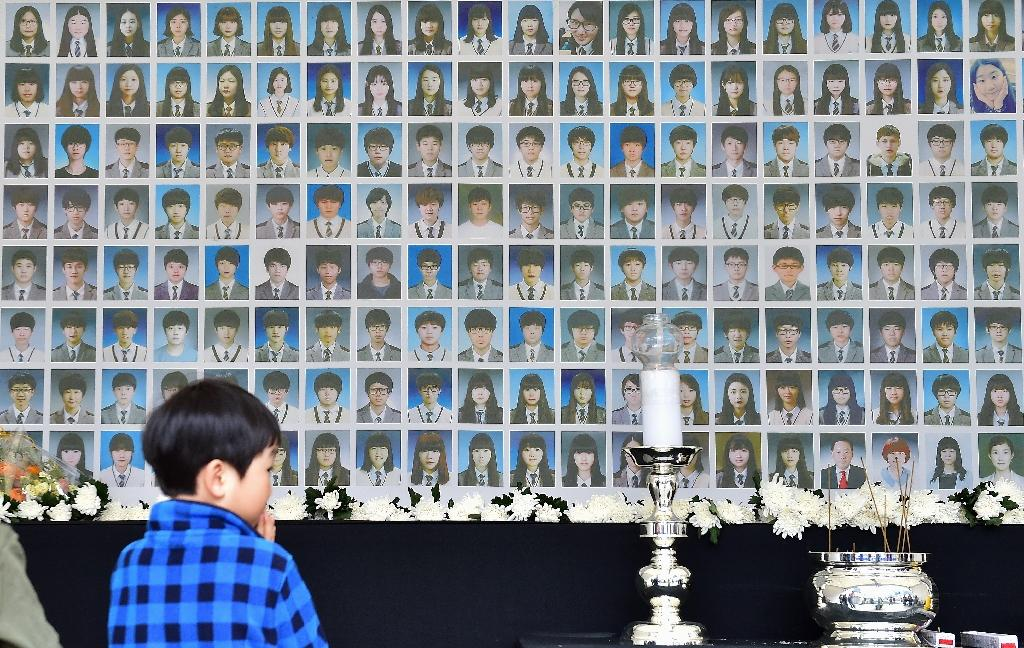 A boy looks at portraits of the victims of South Korea's Sewol ferry disaster at a memorial altar at Gwanghwamun Square in Seoul, on April 15, 2015 (AFP Photo/Jung Yeon-Je)