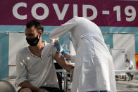 FILE - In this July 12, 2021, file photo, a medical worker administers a shot of Russia's Sputnik V coronavirus vaccine at a vaccination center in Gostinny Dvor, a huge exhibition place in Moscow, Russia. In Russia, it's common to get an antibody test and share the results. The tests are cheap, widely available and actively marketed by private clinics nationwide, and their use appears to be a factor in the country's low vaccination rate even as daily deaths and infections are rising again. (AP Photo/Pavel Golovkin, File)