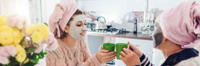 a mom and her adult daughter sipping from coffee cups in a kitchen with facial masks on