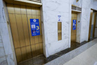 Stickers announce the limit of people allowed in each of the elevators at a Manhattan federal courthouse amid the coronavirus pandemic, Friday, March 12, 2021, in New York. (AP Photo/Mary Altaffer)
