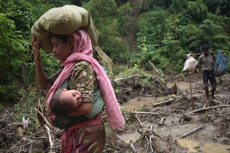A Rohingya woman carries her child in a sling after crossing the border into Bangladesh on Sept. 5, 2017. (Mushfiqul Alam/NurPhoto via Getty Images)
