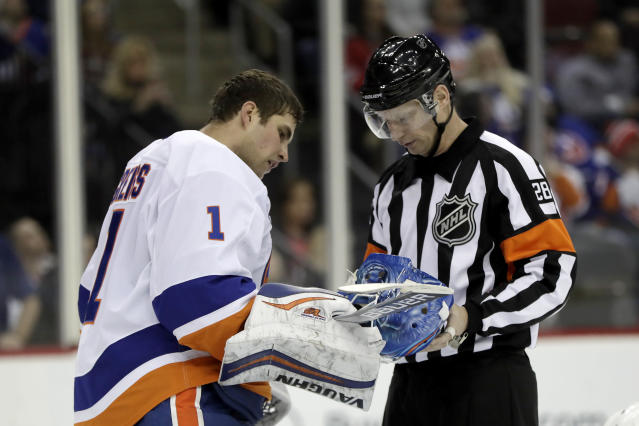 New York Islanders goaltender Thomas Greiss (1), of Germany, shows his helmet to referee Chris Lee (28) between plays against the New Jersey Devils during the second period of an NHL hockey game Thursday, Feb. 7, 2019, in Newark, N.J. (AP Photo/Julio Cortez)