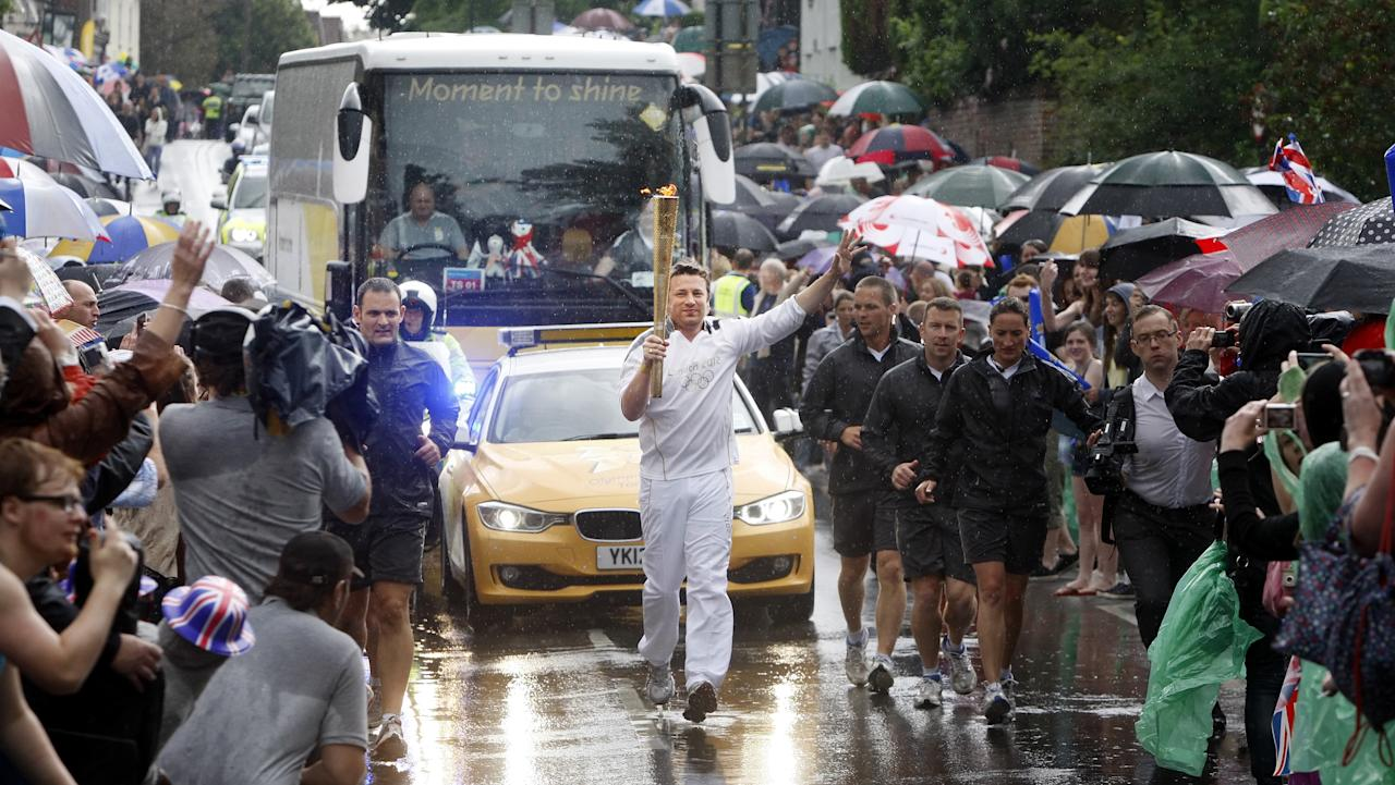 NEWPORT, ENGLAND - JULY 07:  TV Chef and Torchbearer Jamie Oliver carries the Olympic Flame on the Torch Relay journey between Newport and Saffron Walden during Day 50 of the London 2012 Olympic Torch Relay on July 7, 2012 in Newport, England. The Olympic Flame is now on day 50 of a 70-day relay involving 8,000 torchbearers covering 8,000 miles.  (Photo by LOCOG via Getty Images)