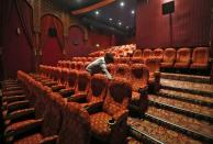 A worker cleans an empty movie theatre after Delhi state government ordered the closure of theatres across the state amid coronavirus fears, in New Delhi