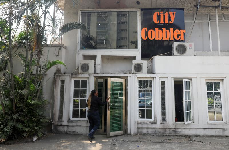 A woman walks into the City Cobbler store in Lagos