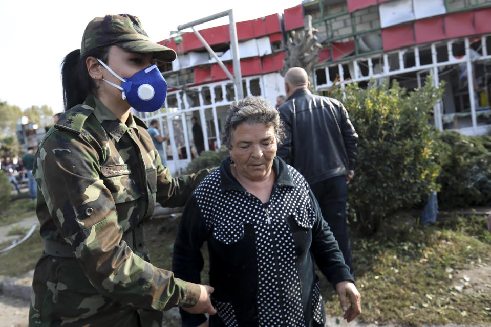 An Azerbaijani officer helps an elderly woman to leave a dangerous area after multiple rocket system shelling by Armenian forces in Barda, Azerbaijan, Wednesday, Oct. 28, 2020. The Azerbaijani Defense Ministry rejected all the accusations and in turn accused Armenian forces of using the Smerch multiple rocket system to fire at the Azerbaijani towns of Terter and Barda. The strike on Barda killed more than 20 people and wounded 60, Azerbaijani officials said. (AP Photo/Aziz Karimov)