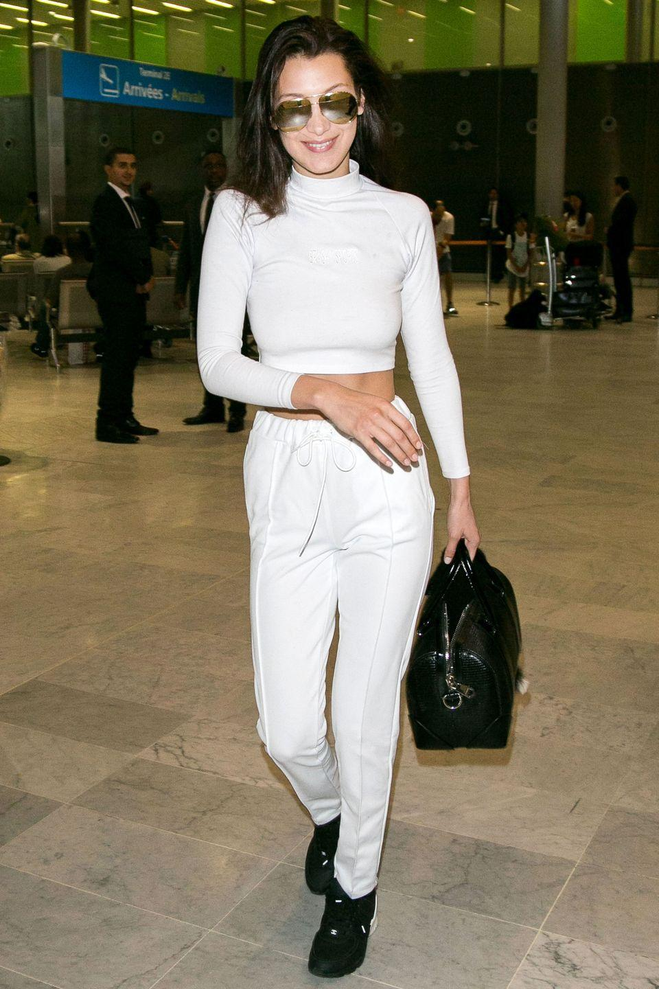 <p>In white turtleneck, white jeans, black bag, sneakers and aviators at Charles-de-Gaulle airport in Paris, France.</p>