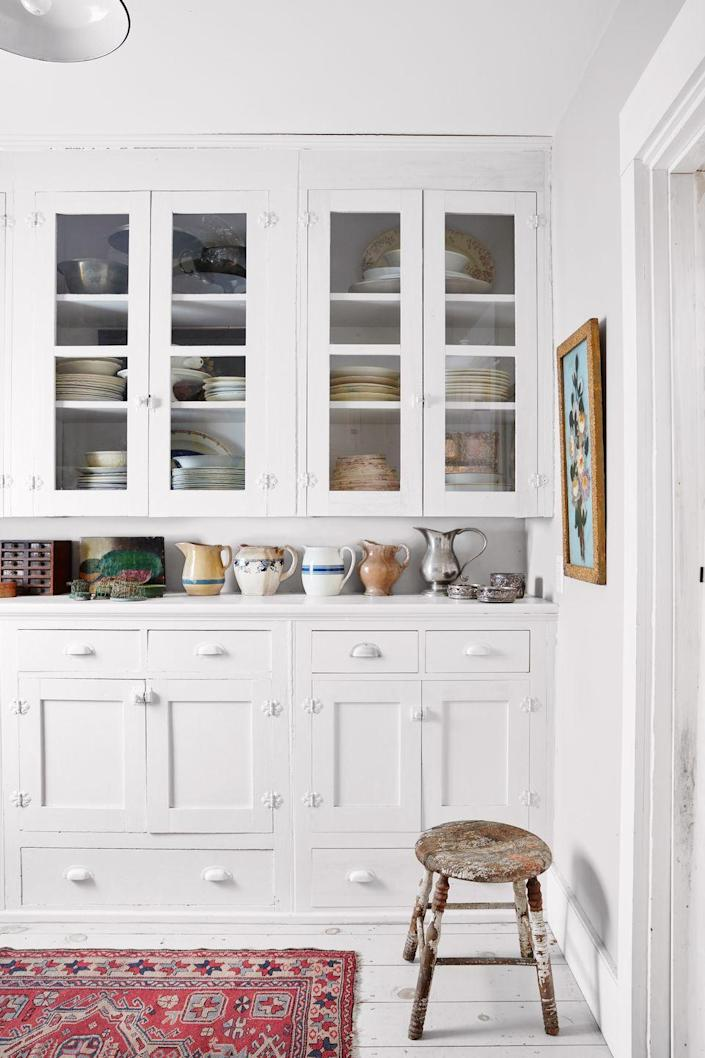 <p>Paint built-ins the same color as walls and floors to create a seamless, intentional design. Collections galore fill these cabinets, shelves, and drawers and add color and character to the all-white space.</p>