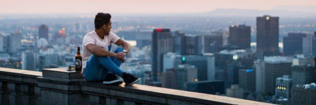 young man sitting on the railing of a building with a beer next to him, overlooking a city