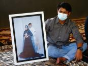 Imam Yoga, 26-year-old brother-in-law of Pandu Yudha Kusuma, 23, one of the crew members of the sunken KRI Nanggala-402 submarine, shows a photograph during an interview at his parents' house in Banyuwangi
