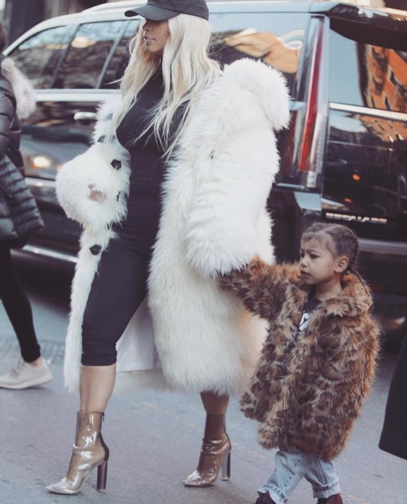 Out in New York City with mom Kim Kardashian, wearing matching furry coats. 2016.