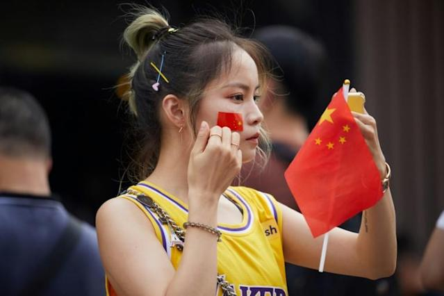 Many spectators at a pre-season game between the Los Angeles Lakers and the Brooklyn Nets in Shenzhen put Chinese flag stickers over their shirts' NBA logo, or held small Chinese flags (AFP Photo/STR)