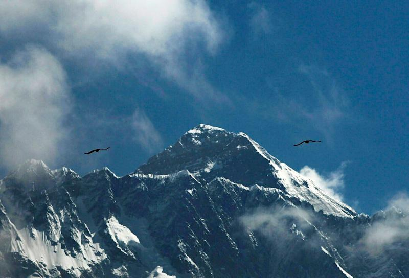Birds fly as Mount Everest is seen from Namche Bajar, Solukhumbu district, Nepal, Monday, May 27, 2019. A Colorado climber died shortly after getting to the top of Mount Everest and achieving his dream of scaling the highest peaks on each of the seven continents, his brother said Monday. (AP Photo/Niranjan Shrestha)