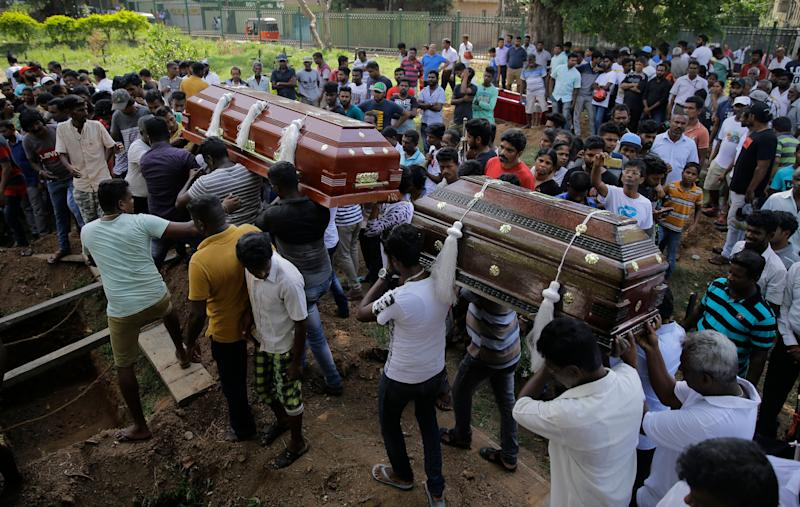 Sri Lankans carry the coffins with the remains of Berington Joseph, left, and Burlington Bevon, right, who were killed in the Easter Sunday bombings in Colombo, Sri Lanka, Tuesday, April 23, 2019. The six near-simultaneous attacks on three churches and three luxury hotels and three related blasts later Sunday were the South Asian island nation's deadliest violence in a decade while Sri Lanka police arrested 40 suspects in the wake of a state of emergency that took effect Tuesday giving the military war-time powers. (AP Photo/Eranga Jayawardena)