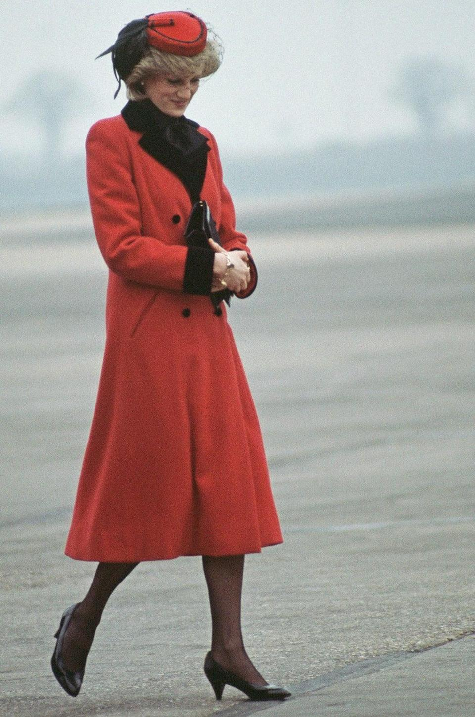 Diana, Princess of Wales wearing a red Catherine Walker coat upon her arrival to Birmingham airport in February 1984 (Jayne Fincher/Princess Diana Archiv)