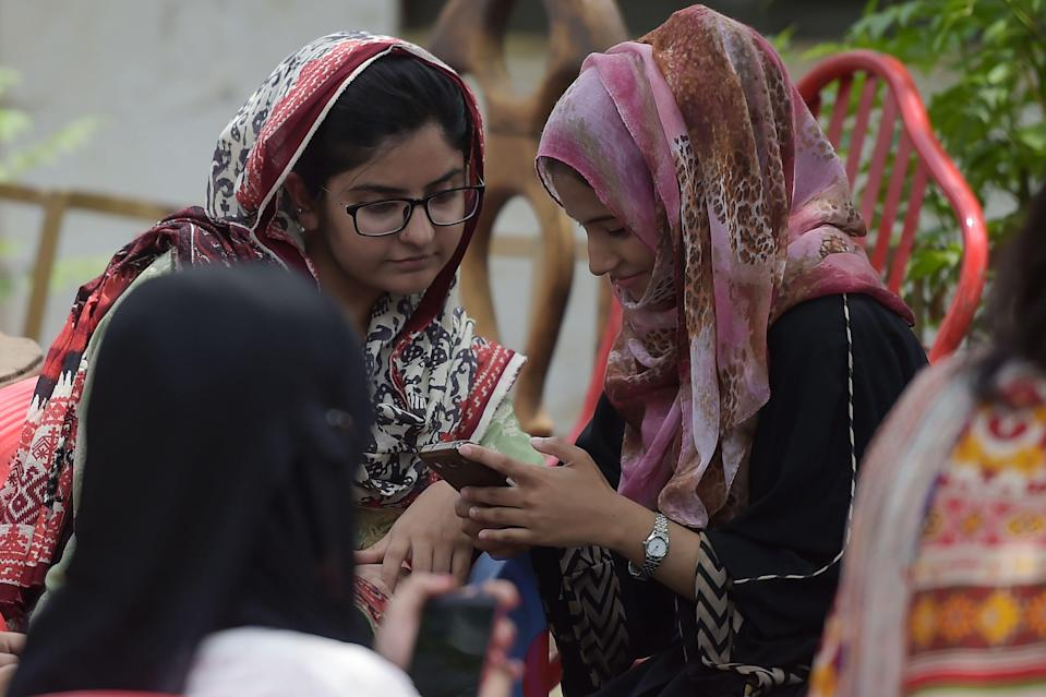 In this picture taken on July 12, 2018, students use their mobile phones at a campus in Islamabad. - A titanic 46 million people below the age of 35 are registered to vote in nationwide elections on July 25 -- many of them savvy social media users who are utilising platforms such as YouTube and Facebook Live to undermine traditional voting patterns by posting videos calling out the powerful. (Photo by Aamir QURESHI / AFP) / To go with PAKISTAN-ELECTIONS-YOUTH-TECHNOLOGY, FOCUS by Gohar ABBAS (Photo credit should read AAMIR QURESHI/AFP via Getty Images)