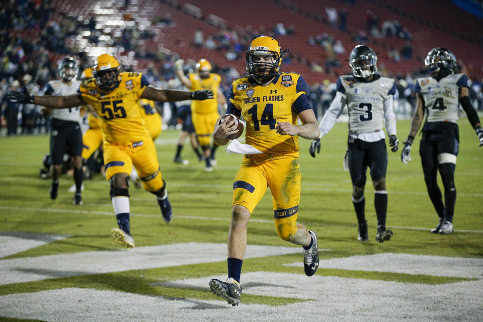 Kent State quarterback Dustin Crum (14) scores a touchdown during the second half of the Frisco Bowl NCAA college football game against Utah State on Friday, Dec. 20, 2019, in Frisco, Texas. Kent State won 51-41. (AP Photo/Brandon Wade)