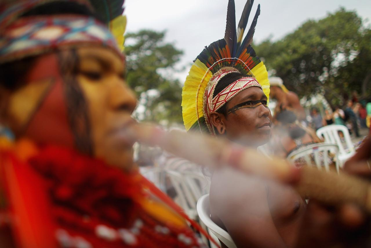 RIO DE JANEIRO, BRAZIL - JUNE 18:  An indigenous man smokes as another looks on at the Rio + 20 counter summit or 'People's Summit' on June 18, 2012 in Rio de Janeiro, Brazil. The People's Summit is financed by the Brazilian government and involves 200 ecological groups and social organizations. Over 100 heads of state and tens of thousands of participants and protesters will descend on Rio de Janeiro, Brazil, June 20-22 for the high-level portion of the Rio+20 United Nations Conference on Sustainable Development or 'Earth Summit'. Host Brazil is caught up in its own dilemma between accelerated growth and environmental preservation. The Brazilian Amazon, home to 60 percent of the world's largest forest and 20 percent of the Earth's oxygen, remains threatened by the rapid development of the country. The summit aims to overcome years of deadlock over environmental concerns and marks the 20th anniversary of the landmark Earth Summit in Rio in 1992, which delivered the Climate Convention and a host of other promises. Brazil is now the world's sixth largest economy and is set to host the 2014 World Cup and 2016 Summer Olympics.  (Photo by Mario Tama/Getty Images)