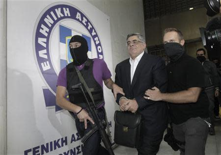 Far-right Golden Dawn party leader Mihaloliakos is escorted by anti-terrorism police officers as he leaves the Greek police headquarters in Athens