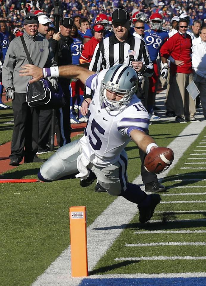 Kansas State quarterback Jake Waters (15) scores a touchdown during the second half of an NCAA college football game against Kansas in Lawrence, Kan., Saturday, Nov. 30, 2013. (AP Photo/Orlin Wagner)