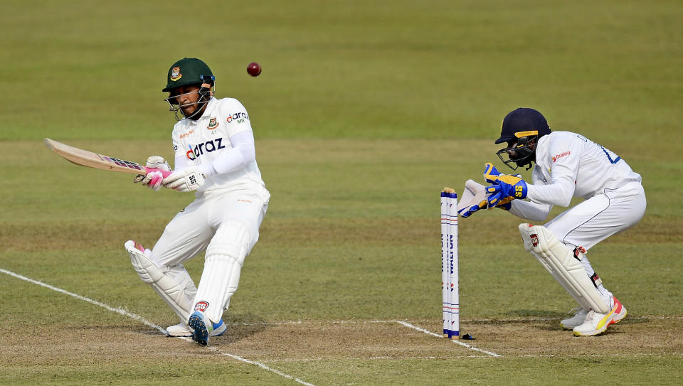 Bangladeshi batsman Mushfiqur Rahim plays a shot as Sri Lankan wicketkeeper Niroshan Dickwella watches during the second day of their first test cricket match in Pallekele, Sri Lanka, Thursday, April 22, 2021.( AP Photo/Sameera Peiris)