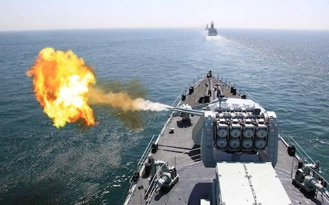In this photo released by China's Xinhua News Agency, Chinese navy's missile destroyer DDG-112 Harbin fires a shell during the China-Russia joint naval exercise in the Yellow Sea - Credit: Xinhua