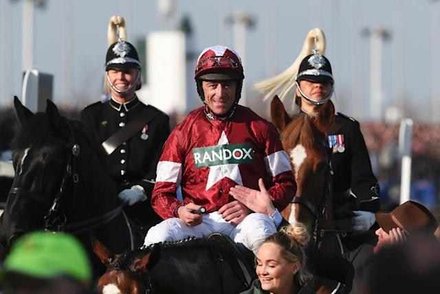 Jockey Davy Russell is led back towards the parade ring after riding Tiger Roll to victory in the Grand National at Aintree Racecourse in Liverpool, northern England on April 14, 2018 (AFP Photo/Jason ROBERTS)