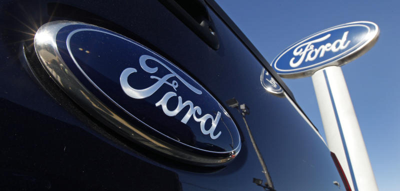 FILE - This Oct. 25, 2011, file photo, shows a Ford logo,on the tailgate of a pick-up truck, and on a Ford dealership sign at Salem Ford in Salem, N.H.  Ford Motor Co. said Friday, April 27, 2012, its net income fell by 45 percent in the first quarter as European sales plummeted and the company paid higher taxes. It earned $1.4 billion, or 35 cents per share, in the first quarter.  (AP Photo/Charles Krupa, File)