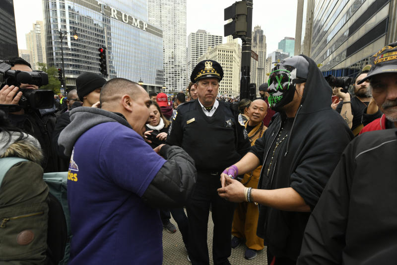 A Trump supporter, left, and protester right, argue while a Chicago police officer center, looks on across the Chicago River from the Trump International Hotel and Tower while President Trump attends a fundraiser Monday, Oct. 28, 2019, in Chicago. (AP Photo/Paul Beaty)
