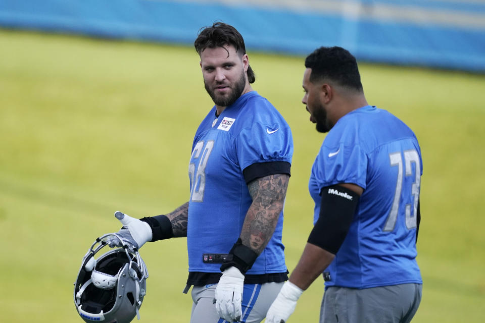 Detroit Lions tackle Taylor Decker, left, and guard Jonah Jackson walk to the field before drills at the Lions NFL football camp practice, Wednesday, July 28, 2021, in Allen Park, Mich. (AP Photo/Carlos Osorio)