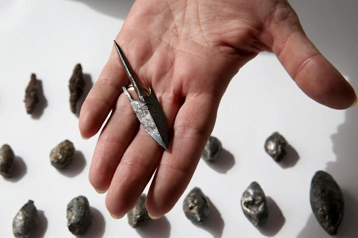 A member of the Israeli Antiquity Authorities displays on November 3, 2015 lead sling stones, bronze arrowheads and ballista stones at a site adjacent to Jerusalem's Old City walls where researchers claim to have found the remains of the Acra (AFP Photo/Gali Tibbon)