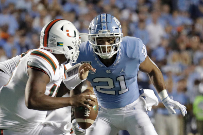FILE - In this Sept. 7, 2019, file photo, Miami quarterback Jarren Williams (15) is pressured by North Carolina's Chazz Surratt (21) during the first half of an NCAA college football game in Chapel Hill, N.C. The North Carolina-Wake Forest game will put brothers Sage and Chazz Surratt on opposite sides for the first time. Sage is a top receiver for the Demon Deacons, while Chazz has moved from quarterback to linebacker for the Tar Heels -- raising the odds that the two meet in a collision at some point Friday night. (AP Photo/Chris Seward, File)