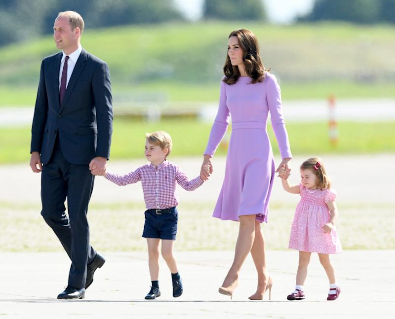 The duke and duchess hold hands with George and Charlotte during a royal visit to Poland and Germany in 2017.