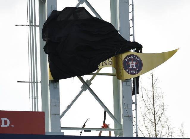 Workers try to remove the cover of the Houston Astros' 2018 World Series champion banner before a baseball game against the Baltimore Orioles. (AP Photo/Eric Christian Smith)