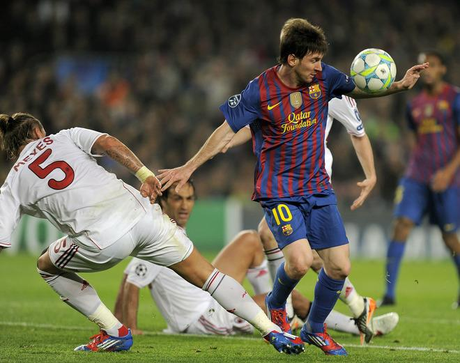 AC Milan's French defender Philippe Mexes (L) fights for the ball with Barcelona's Argentinian forward Lionel Messi  during the Champions League quarter-final second leg football match FC Barcelona vs AC Milan on April 3, 2012 at Camp Nou stadium in Barcelona.   AFP PHOTO / LLUIS GENE