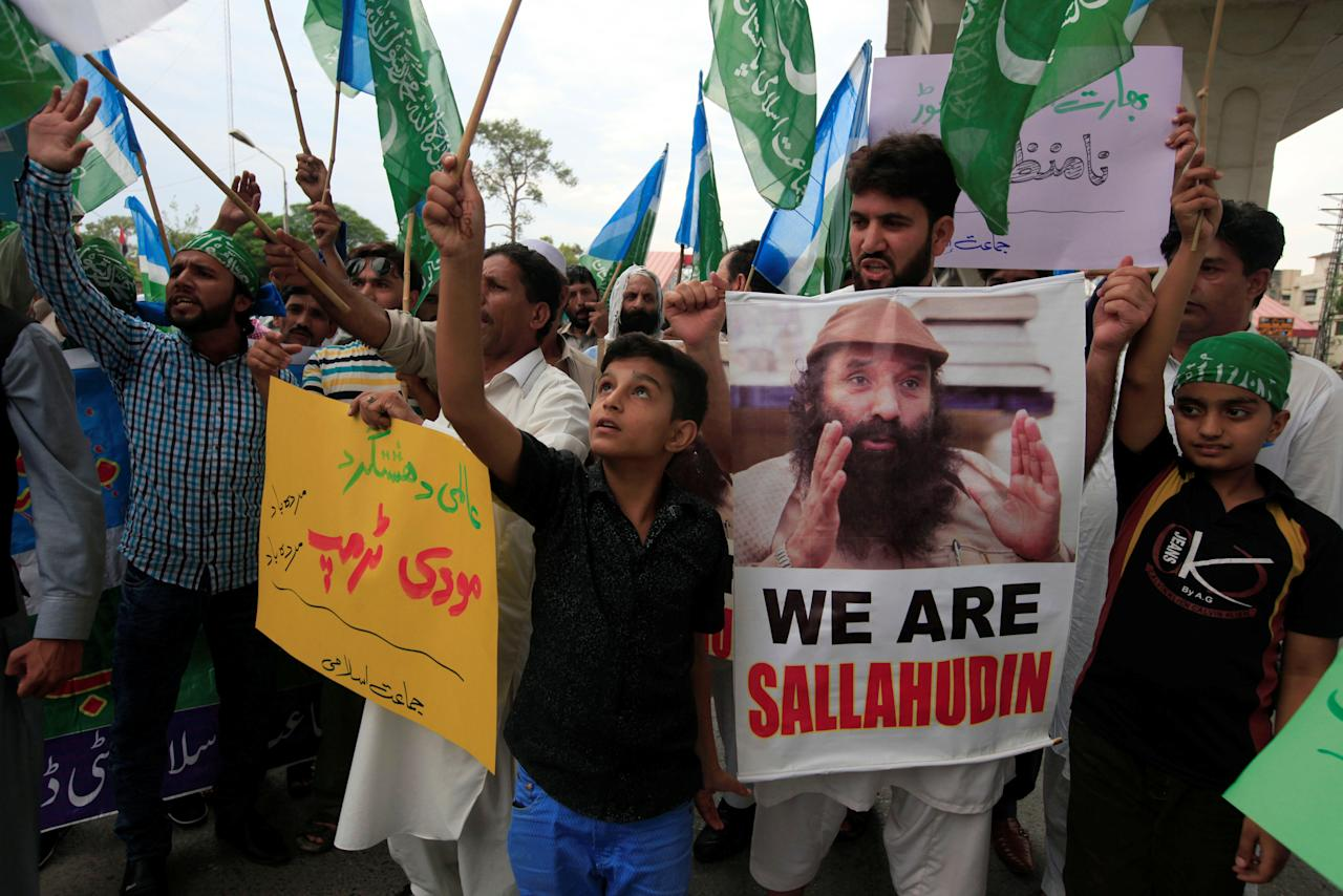 Supporters of religious and political party Jamaat-e-Islami (JI) chant slogans during a protest against the U.S. decision of putting the leader of an anti-India militant group Syed Salahuddin (seen in the image) on its list of global terrorists, in Rawalpindi, Pakistan June 28, 2017. REUTERS/Faisal Mahmood