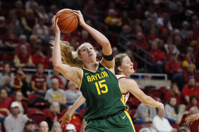 FILE - In this Sunday, March 8, 2020 file photo, Baylor forward Lauren Cox (15) catches a pass ahead of Iowa State guard Ashley Joens, rear, during an NCAA college basketball game in Ames, Iowa. Lauren Cox is still trying to process that her college basketball career is over. The Baylor forward, like many other seniors, saw her season end when the NCAA Tournament was canceled. She was on a plane with her teammates ready to head to the Big 12 Tournament last week when word came that the conference had canned its postseason.(AP Photo/Charlie Neibergall, File)