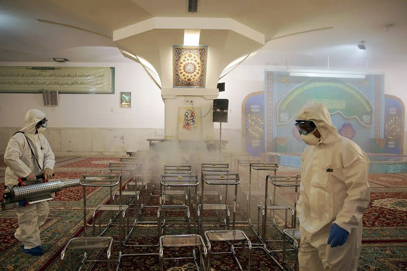 Members of the medical team spray disinfectant to sanitize indoor place of Imam Reza's holy shrine, following the coronavirus outbreak, in Mashhad