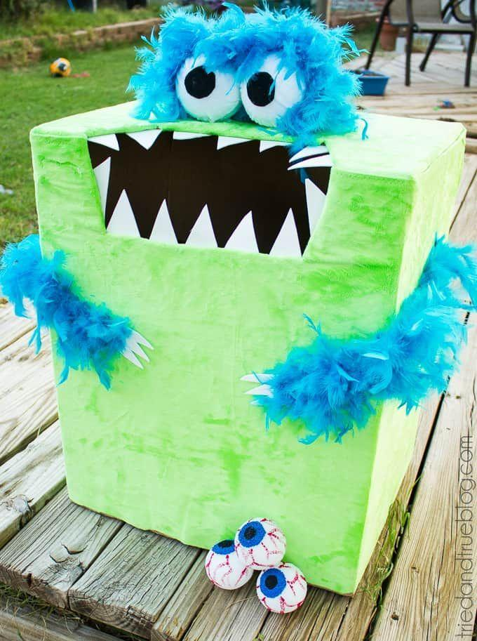 """<p>If you have a cardboard box lying around, dress it up like a monster by taking apart a <a href=""""https://www.amazon.com/SACAS-Fashion-Feather-Chandelle-Turquoise/dp/B00H9ZNEHU?tag=syn-yahoo-20&ascsubtag=%5Bartid%7C10055.g.2618%5Bsrc%7Cyahoo-us"""" rel=""""nofollow noopener"""" target=""""_blank"""" data-ylk=""""slk:feathered boa"""" class=""""link rapid-noclick-resp"""">feathered boa</a> and use it as a spooky alternative to a bean-bag toss. </p><p><em><a href=""""http://www.triedandtrueblog.com/feed-the-monster-halloween-game/"""" rel=""""nofollow noopener"""" target=""""_blank"""" data-ylk=""""slk:Get the tutorial at Tried & True »"""" class=""""link rapid-noclick-resp"""">Get the tutorial at Tried & True »</a></em></p>"""