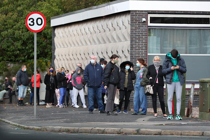 People queuing outside a walk-in coronavirus test centre at Allerton Library in Liverpool amid rising cases across parts of England, with the latest weekly infection figures showing Knowsley and Liverpool have the second and third highest rates, at 498.5 and 487.1 respectively. (Photo by Peter Byrne/PA Images via Getty Images)