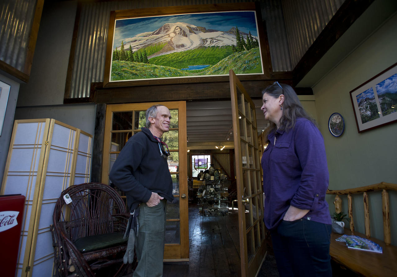 Furloughed park ranger Rich Lechleitner, left, visits with friend Jana Gardiner co-owner of Ashford Creek Pottery Tuesday Oct. 15, 2013 as Mount Rainier National Park in Washington remained closed due to the partial government shutdown. Gardiner, a 33 year resident of Ashford has seen only a trickle of visitors since the shutdown closed Mount Rainier National Park. (AP Photo/The News Tribune, Dean J. Koepfler)