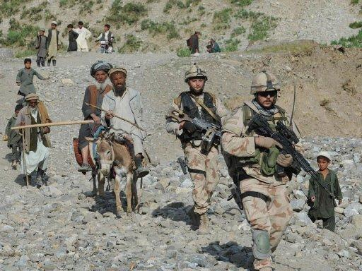 NATO-led International Security Assistance Force (ISAF) soldiers walk with Afghan villagers in Baghlan province