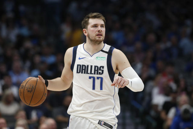FILE - In this March 11, 2020, file photo, Dallas Mavericks guard Luka Doncic (77) handles the ball against the Denver Nuggets during the second half of an NBA basketball game in Dallas. Video games have become a go-to hobby for millions self-isolating around the world, and athletes from preps to pros have eagerly grabbed the controls. Stars like Ben Simmons and Luka Doncic have turned to gaming to stay connected with fans.(AP Photo/Ron Jenkins, File)