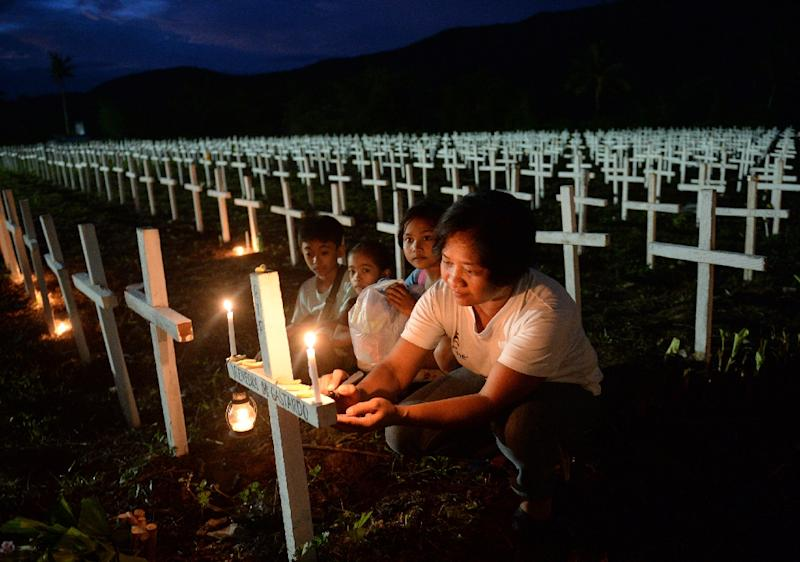 A woman, accompanied by her young family members, writes the name of a loved one on a cross at a mass graveyard for victims of typhoon Haiyan, in Tacloban City, Leyte province, central Philippines, in November 2015