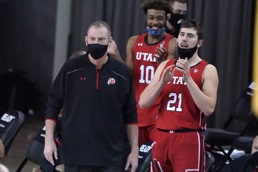 Utah coach Larry Krystkowiak, left, watches his team play against UCLA during the first half of an NCAA college basketball game Thursday, Dec. 31, 2020, in Los Angeles. (AP Photo/Marcio Jose Sanchez)