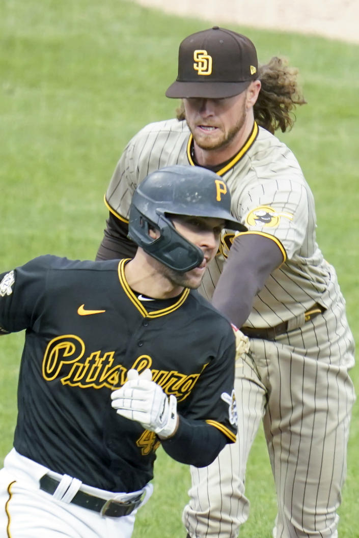 San Diego Padres starting pitcher Chris Paddack, top, tags out Pittsburgh Pirates' Adam Frazier as he heads to first after hitting a ground ball in the second inning of a baseball game, Thursday, April 15, 2021, in Pittsburgh. (AP Photo/Keith Srakocic)