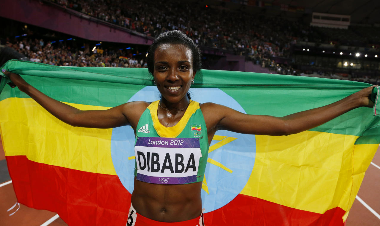 Ethiopia's Tirunesh Dibaba celebrates with her national flag after she won the women's 10,000m final at the London 2012 Olympic Games at the Olympic Stadium August 3, 2012. REUTERS/Phil Noble (BRITAIN  - Tags: SPORT ATHLETICS OLYMPICS)