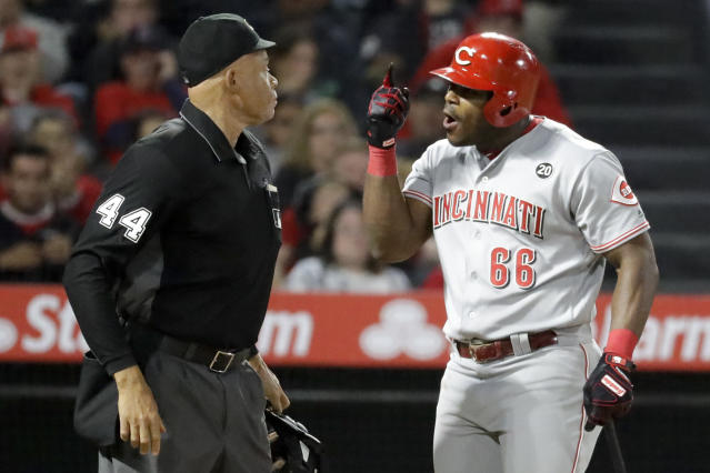 Cincinnati Reds' Yasiel Puig, right, has words with home plate umpire Kerwin Danley after being thrown out of the team's baseball game against the Los Angeles Angels during the sixth inning in Anaheim, Calif., Tuesday, June 25, 2019. (AP Photo/Chris Carlson)